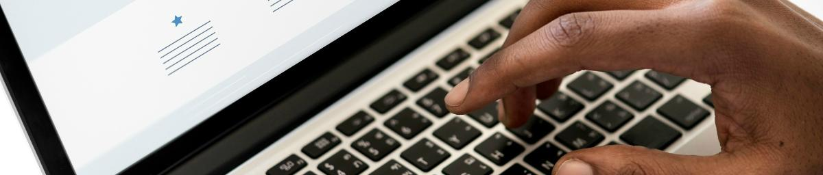 Close-up image of a hand typing on a laptop keyboard